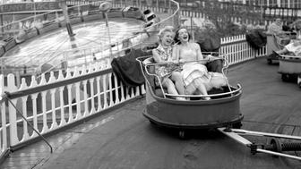 BROOKLYN - MAY 11: Models from the CBS gameshow, 'The Big Payoff,' Cindy Robbins and Pat Conway ride The Whip designed and built by W.F. Mangels Company of Coney Island, at Steeplechase Park. Coney Island, Brooklyn, NY. Image dated May 11, 1953. (Photo by CBS via Getty Images)