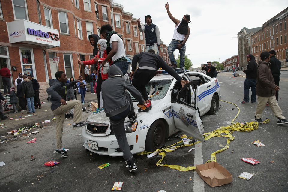 BALTIMORE, MD - APRIL 27:  Demonstrators climb on a destroyed Baltimore Police car in the street near the corner of Pennsylva