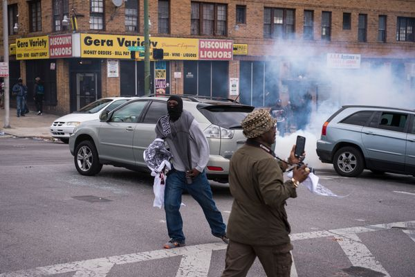 BALTIMORE, MD - APRIL 27: People run as smoke and tear gas is thrown during a protest for Freddie Gray near Mondawmin Mall in