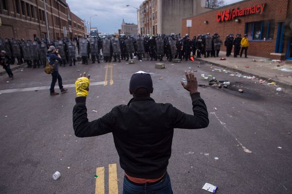 BALTIMORE, MD - APRIL 27: People stand with their hands up as officers move toward them near a CVS pharmacy near West North A