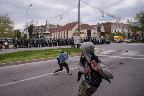 BALTIMORE, MD - APRIL 27: A man throws an object at officers during a protest for Freddie Gray near Mondawmin Mall in Baltimo