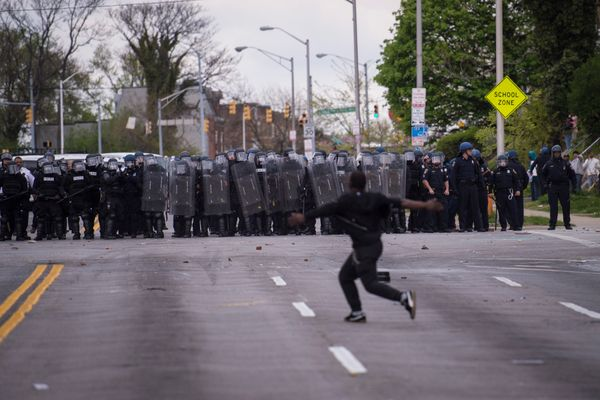 BALTIMORE, MD - APRIL 27: A man runs in front of officers during a protest for Freddie Gray near Mondawmin Mall in Baltimore,