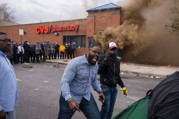BALTIMORE, MD - APRIL 27: A protestor yells as a CVS burns near West North Avenue and Pennsylvania Avenue during a protest fo