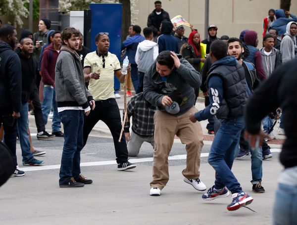 A man, center, shields himself after being struck after a march to City Hall for Freddie Gray, Saturday, April 25, 2015 in Ba