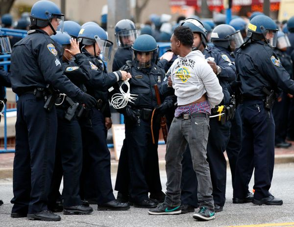 Police detain a man after a march to City Hall for Freddie Gray, Saturday, April 25, 2015 in Baltimore. Gray died from spinal