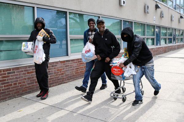 Men carry items, Monday, April 27, 2015, during unrest following the funeral of Freddie Gray in Baltimore. Gray died from spi