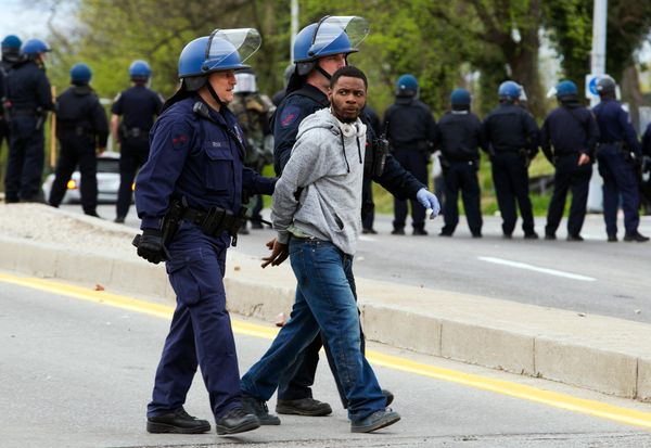 Baltimore police officers detain a demonstrator after the funeral of Freddie Gray, Monday, April 27, 2015, in Baltimore. (AP
