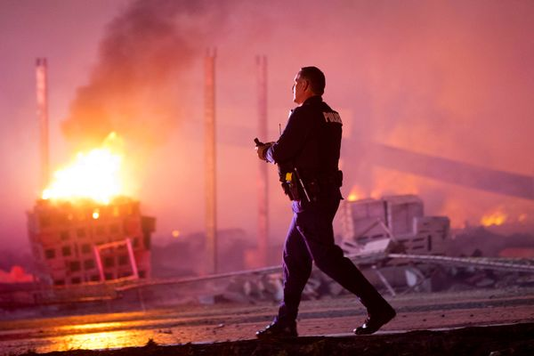 A police officer walks by a blaze, Monday, April 27, 2015, after rioters plunged part of Baltimore into chaos, torching a pha