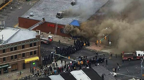 In this frame from video provided by WJLA, smoke rises from a store Monday, April 27, 2015, during unrest following the funer