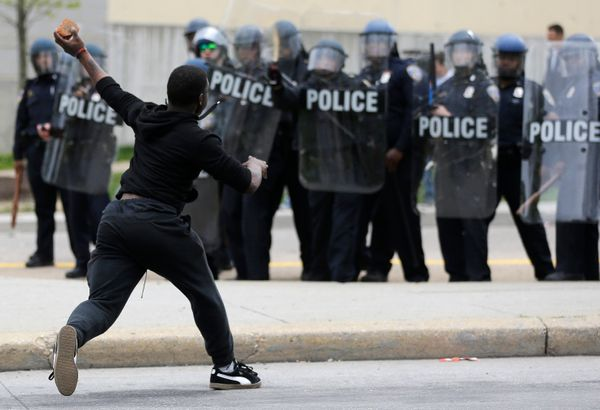 A man throws a brick at police Monday, April 27, 2015, following the funeral of Freddie Gray in Baltimore. (AP Photo/Patrick