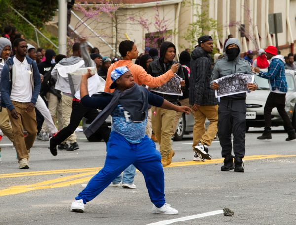 Demonstrators throw rocks at the police, after the funeral of Freddie Gray, on Monday, April 27, 2015, at New Shiloh Baptist