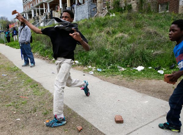A boy throws a brick at police, Monday, April 27, 2015, during unrest following the funeral of Freddie Gray in Baltimore. (AP