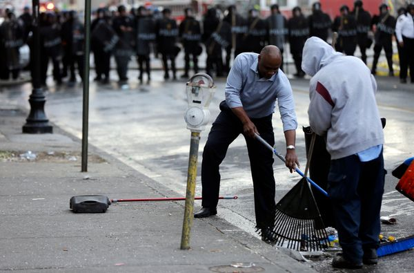 Men clean up during a protest, Monday, April 27, 2015, following the funeral of Freddie Gray in Baltimore.  (AP Photo/Matt Ro
