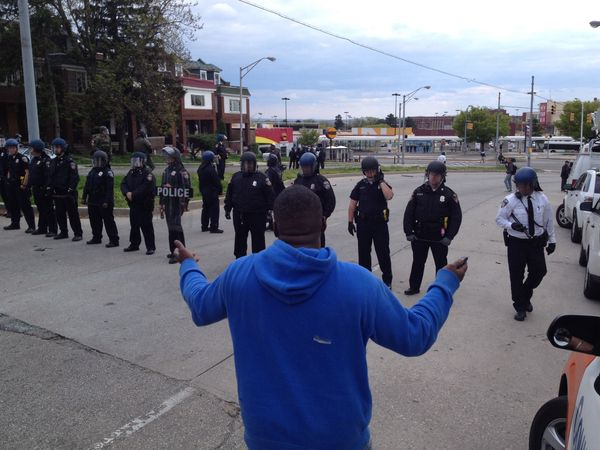 Police maintain a line at Liberty Heights and Reisterstown Road in Baltimore during protests on Monday, April 27, 2015. Photo
