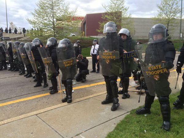 State troopers and police line up in protective gear at Monroe and Gwynns Falls Parkway in Baltimore during protests on Monda