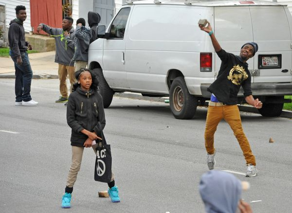 Protesters throw rocks at the line of police in riot gear on North Monroe Street near Bryant Avenue during riots on Monday, A