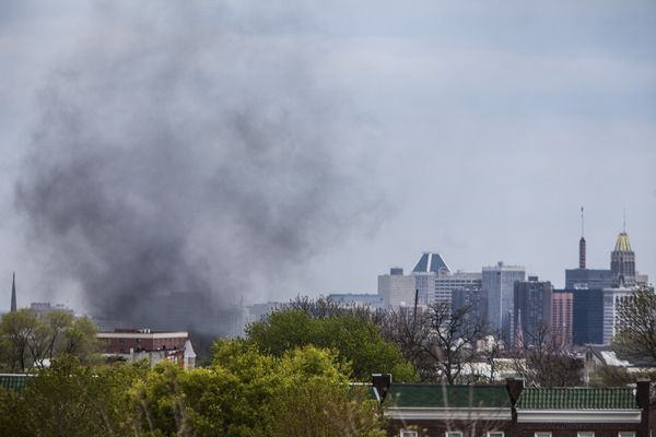 WASHINGTON, USA - APRIL 27: Smoke from a burning car set on fire by protestors rises over the Baltimore skyline during riots