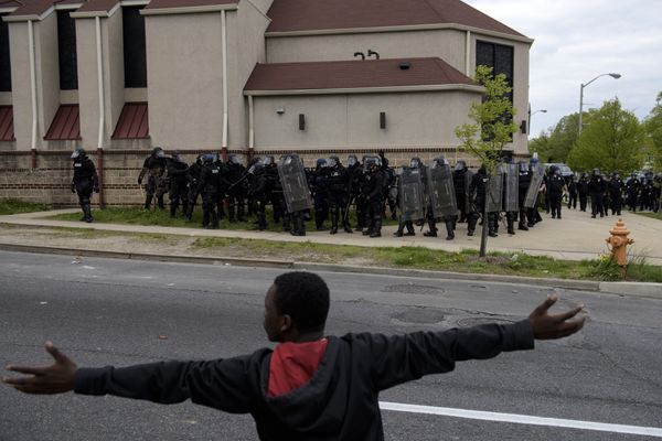 A protestor gestures before riot police on April 27, 2015 in Baltimore, Maryland on April 27, 2015 in Baltimore, Maryland.  V