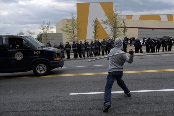 A man throws a wood board at police on April 27, 2015 in Baltimore, Maryland.   Violent street clashes erupted in Baltimore a