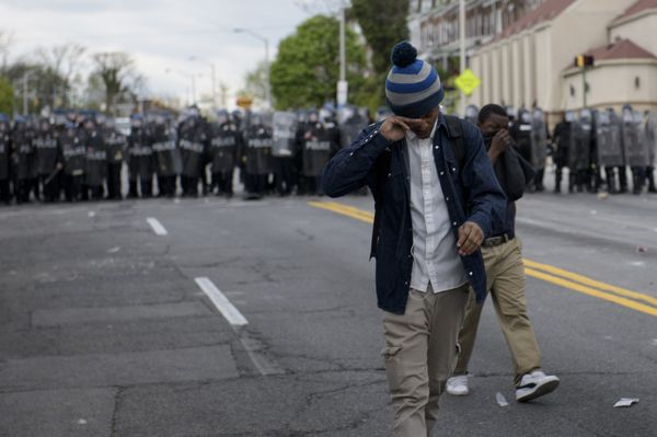 A protester wipes his eyes after police used pepper balls on April 27, 2015 in Baltimore, Maryland.   Violent street clashes