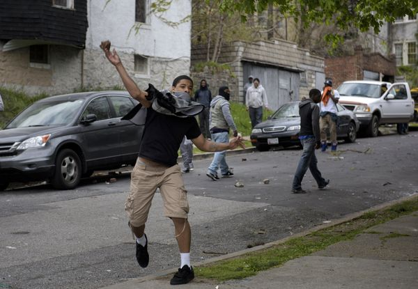 A youth throws a rock at police on April 27, 2015 in Baltimore, Maryland.  Violent street clashes erupted in Baltimore after