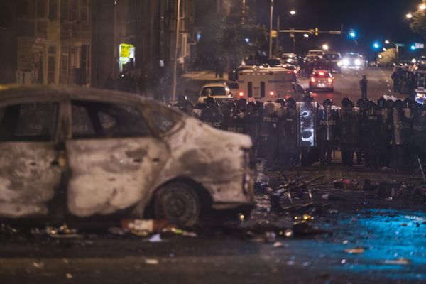 WASHINGTON, USA - APRIL 27: Police retreat from the hulks of burned out cars in the middle of an intersection during riots in