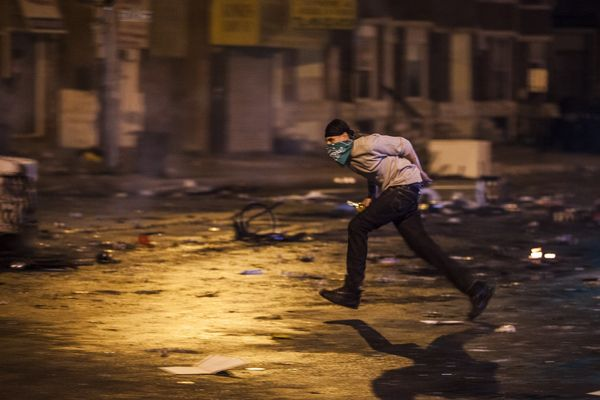 WASHINGTON, USA - APRIL 27: A rioter runs for cover as police fire non-lethal rounds at him during riots in Baltimore, USA on