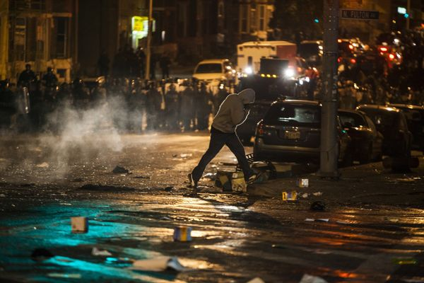 WASHINGTON, USA - APRIL 27: A man crosses the street over burning debris between police and rioters during riots in Baltimore