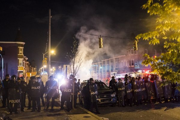 WASHINGTON, USA - APRIL 27: Police for a line in front of burned out cars during riots in Baltimore, USA on April 27, 2015. P