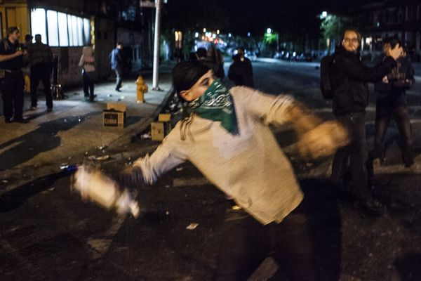 WASHINGTON, USA - APRIL 27: A protestor throws a liquor bottle at police lines during riots in Baltimore, USA on April 27, 20