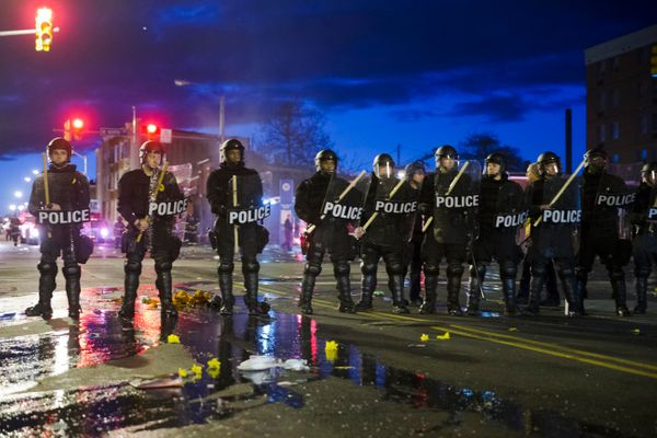 Police stand guard Monday, April 27, 2015, after rioters plunged part of Baltimore into chaos, torching a pharmacy, setting p