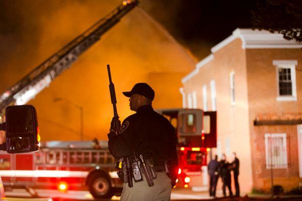 An officer stands near a blaze, Monday, April 27, 2015, after rioters plunged part of Baltimore into chaos, torching a pharma