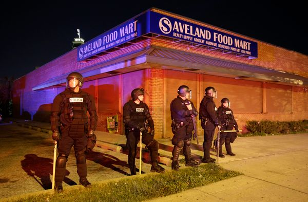 Police stand outside a shuttered store, Monday, April 27, 2015, during unrest following the funeral of Freddie Gray in Baltim