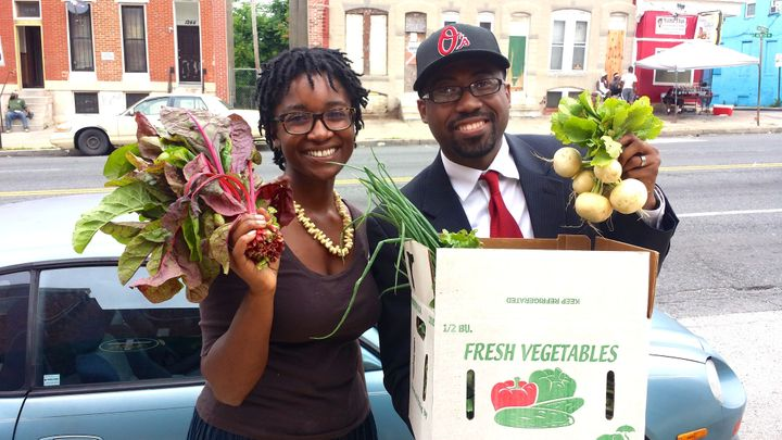 Rev. Heber Brown III and Aleya Fraser, co-founder of Black Dirt Farm, hold up produce from the farm.