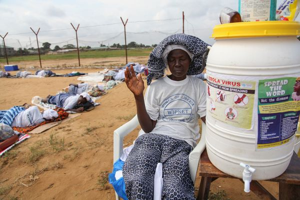 A Liberian woman prays for God's intervention in eradicating Ebola during a Women in Peace building Program (WIPNET) official