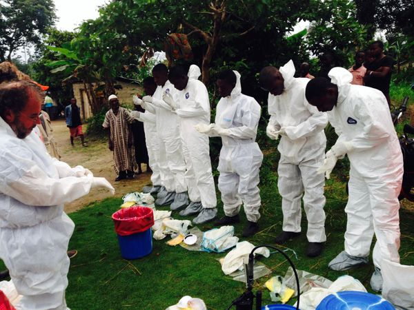 Volunteers prepare to remove the bodies of people who were suspected of contracting Ebola and died in the community in the vi