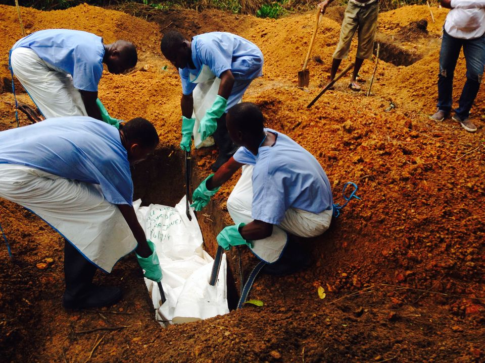 Volunteers lower a corpse, which is prepared with safe burial practices to ensure it does not pose a health risk to others an