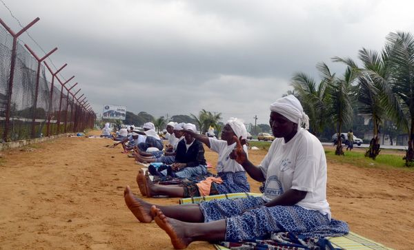 Members of Women in Peace Building Networkpray on a field not far from the residence of Liberia's president, in Monrovia, to