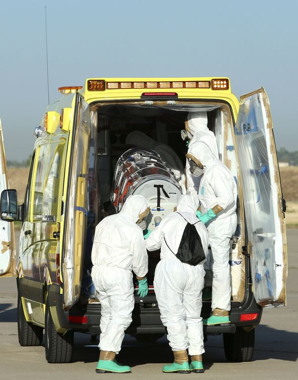 A handout photo released by the Spanish Defense Ministry shows several paramedics wearing protective suits as they mov Spanis