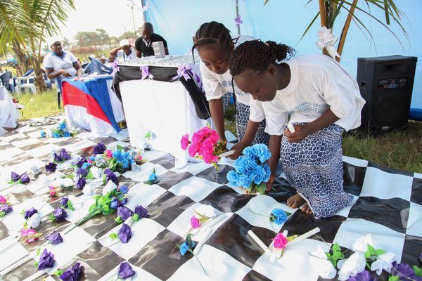 Liberian children lay flowers in memory of all Liberians who have died of the Ebola virus at the Women in Peace building Prog