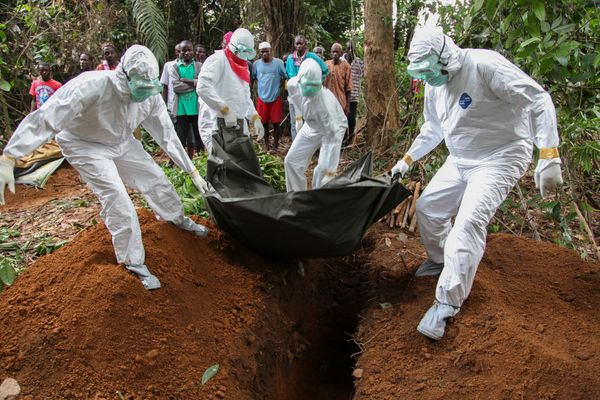 Liberian nurses bury the body of an Ebola victim in the Banjor Community on the outskirts of Monrovia, Liberia 06 August 2014