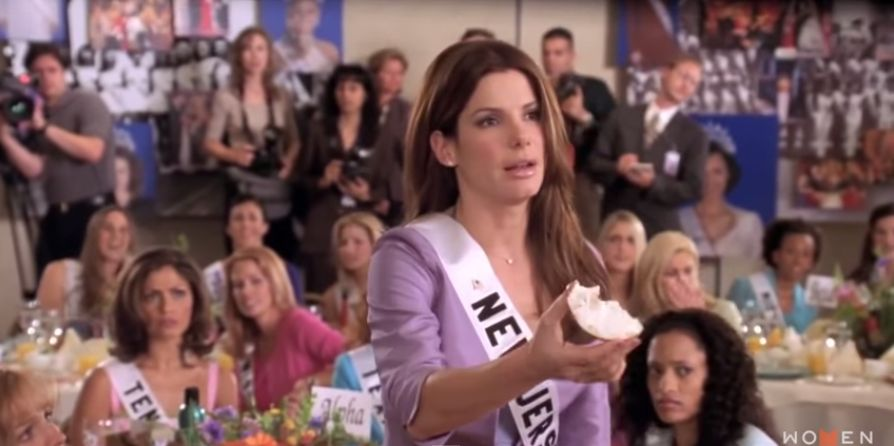 "Sandra Bullock in the movie ""Miss Congeniality"" apologizing for eating a bite of her bagel before praying."