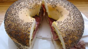 Poppy seed bagel with hot salt beef, gherkins and mustard.