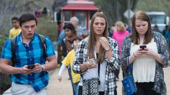 Three  teens walk with their smartphones as they walk outside the Natural History Museum  in Washington on April 8, 2015. A Pew Research Center survey released found that 92 percent of US teens go online daily. The survey of teens between the ages of 13 and 17 found that 73 percent had a smartphone and 30 percent had at least a basic cellphone.   AFP PHOTO/ NICHOLAS KAMM        (Photo credit should read NICHOLAS KAMM/AFP/Getty Images)