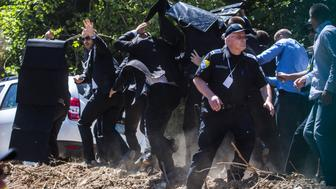 SREBRENICA, BOSNIA AND HERZEGOVINA - JULY 11:  Bodyguards use umbrella and protection to protect Prime Minister of Serbia Aleksandar Vucic during unrest at the Potocari cemetery and memorial near Srebrenica on July 11, 2015 in Srebrenica, Bosnia and Herzegovina. The newly-identified remains of another 136 victims from Srebrenica massacre were buried at the ceremony on the 20th anniversary of the massacre. At least 8,3000 Bosnian Muslim men and boys who had sought safe heaven at the U.N.-protected enclave at Srebrenica were killed by members of the Republic of Serbia (Republika Srpska) army under the leadership of General Ratko Mladic, who is currently facing charges of war crimes at The Hague, during the Bosnian war in 1995.  (Photo by Matej Divizna/Getty Images)