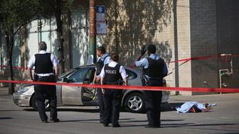 CHICAGO, IL - JULY 11:  (EDITORS NOTE: Image contains graphic content) Chicago police invesitgate a shooting death on July 11, 2013 in Chicago, Illinois. A 27-year-old man died on the scene after being shot in the chest. Chicago has had more than 200 homicides so far in 2013 and has had more than 1000 people shot. There have been more than 21 murders in July.  (Photo by Scott Olson/Getty Images)