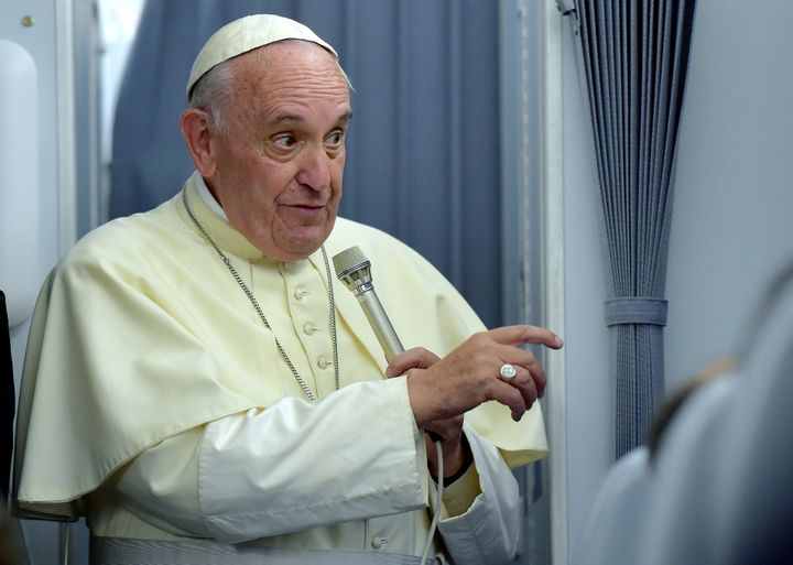 Pope Francis gestures to journalists during a press conference on July 13, 2015, onboard a plane on his way back to Rome from