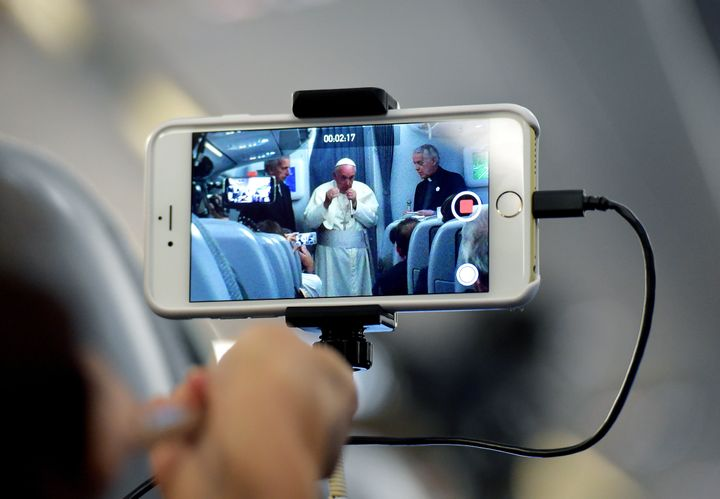 A journalist takes with his mobile phone a picture of Pope Francis during a press conference on July 13, 2015, onboard a plan