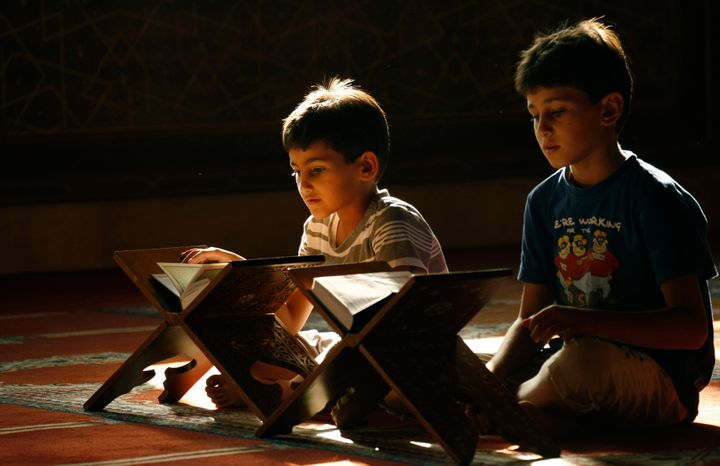 Lebanese Muslim boys read from the Koran, Islam's holy book, during the holy fasting month of Ramadan, at a mosque in the sou