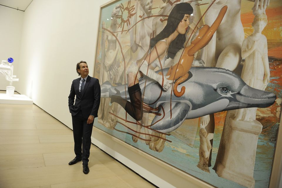 US artist Jeff Koons poses past one of his piece of art during the presentation of the 'Jeff Koons: Retrospective' exhibition